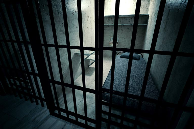 Photo of the inside of a dark jail cell