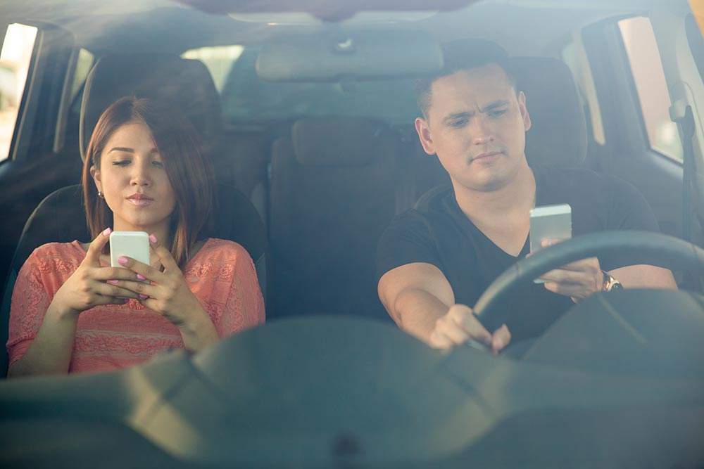 Photo of distracted driver looking at his phone